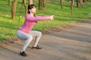Junge Frau mit duklen Haaren und rosa Pulli macht Kniebeugen im Park