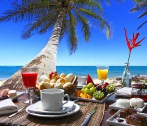 Frühstücksbuffet am Strand mit Palme und Meer
