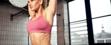 Junge, blonde Frau mit rosa Sport Top stemmt beim CrossFit Training eine Langhantel über Kopf