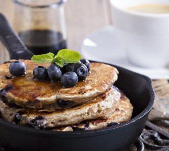 Pancakes in einer schwarzen Pfanne mit Blaubeeren garniert
