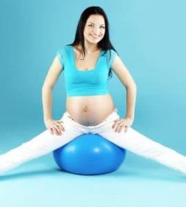 Junge, schwangere Frau mit braunen Haaren und weißer Hode sitzt auf einem blauen Pezziball vor türkisem Hintergrund