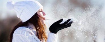 Frau mit weißer Mütze und Schal pustet Schnee aus ihren Händen
