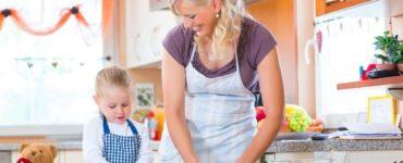 Mutter und Kind mit Schürze backen Plätzchen