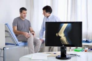 Behalndlungszimmer, Arzt und Patient, Bildschirm mit Röntgenbild eines Knies