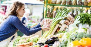 Frau steht am Gemüseregal und greift einen Beutel Kartoffeln.