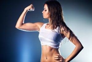 Durchtrainierte Frau spannt nach ihrem Workout ihren Bizeps an