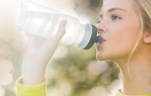 Frau trinkt Wasser aus Flasche