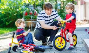 Vater repariert mit seinen beiden Kindern ein Kinderrad.