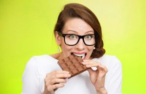 Frau beißt in eine Tafel Schokolade