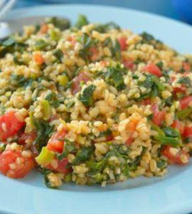 Bulgur mit Spinat und Tomate auf einem hellblauen Teller