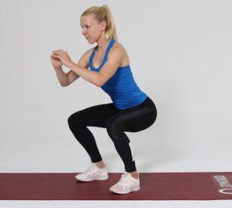 Frau macht Squat auf roter Trainingsmatte