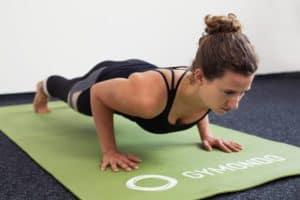 Junge Frau in Liegestützposition auf einer hellgrünen Trainingsmatte macht Push Ups