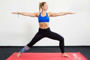 Junge Frau auf einer roten Trainingsmatte macht den Krieger 2 aus dem Yoga