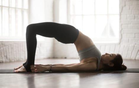 Frau macht Yoga die Brücke