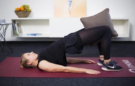 Junge Frau auf Trainingsmatte zu Hause macht Übung für den Beckenboden