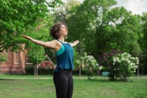 Junge Frau auf einer Raststätte macht Übung Brust Stretch