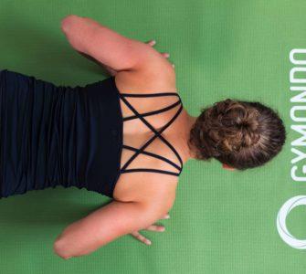 Junge Frau auf einer hellgrünen Trainingsmatte macht Liegestützen