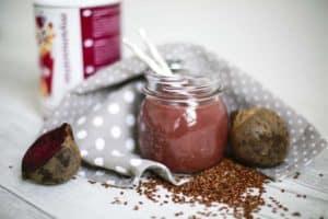 Dunkelroter Smoothie in Glas auf Tisch dekoriert mit mysmoothie Flakes und Leinsamen