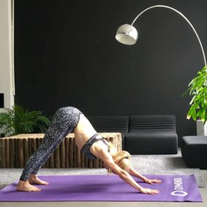 Frau macht Yoga Sonnengruß Down Dog auf lila trainingsmatte