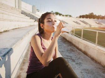 Sportlerin trinkt Wasser nach dem Workout.