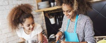 Mutter und Kind kochen gemeinsam gesund in der Küche
