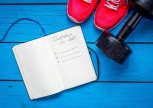 Gute Vorsätze für mehr Sport im neuen Jahr mit Sportschuhen, Hantel und Notizbuch auf blauen Dielen