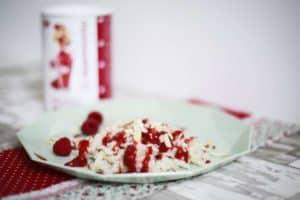 Reispudding mit Smoothie Flakes uaf hellgrünem Teller auf Tisch, im Hintergrund mysmoothie Flakes