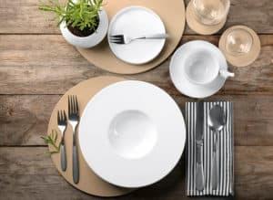 Gedeckter Holz-Tisch mit Teller, Tasse und Besteck