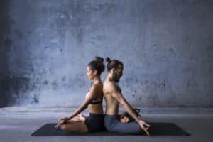 Frau und Mann sitzen Rücken an Rücken und machen Yoga
