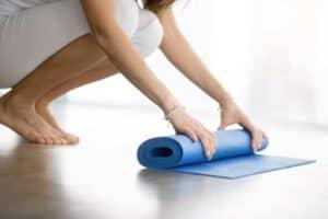 Frau rollt eine Fitness-Matte zusammen