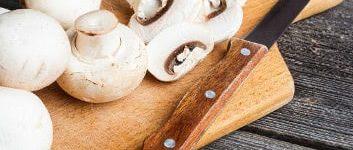 Weiße Champignons und ein Messer auf einem Holzbrett, zum Teil am Stück, zum Teil geschnitten