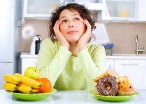 Frau, die zwischen gesundem und ungesundem Essen hin- und hergerissen ist