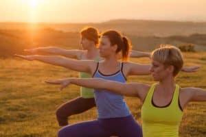 """Sportlerinnen machen die Gleichgewichtsübung """"Krieger 3"""""""