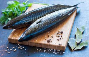 Zwei frische blaue Makrelen auf einem Holzbrett