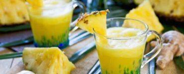 Ananas-Smoothie mit Ingwer in einem Glas, das mit 1/8 Ananasscheibe dekoriert wurde.
