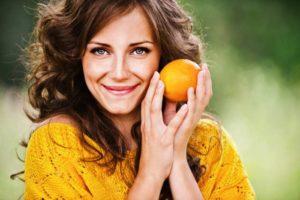 Glückliche Frau mit schönem Haar hält eine Orange an ihr Gesicht