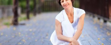Frau Mitte 50 in weißer Sportkleidung sitzt auf blauer Trainingsmatte und lächelt glücklich und entspannt