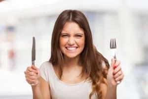 Frau mit Messer und Gabel in den Händen grinst