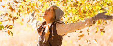 Junge Frau mit Jacke und Mütze streckt die Arme nach oben und ist glücklich. Herbst Laub fliegt im Hintergrund durch die Luft