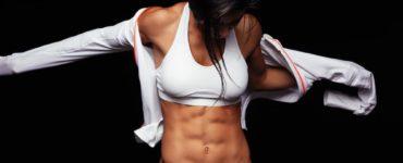 Frau mit durchtrainiertem Körper in Sportkleidung breitet die Arme aus und blickt auf ihr Sixpack