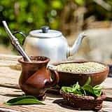 Teekanne mit Mate Tee auf Holztisch, braune Mate Tee Tasse und Schale mit Mate Tee Pulver