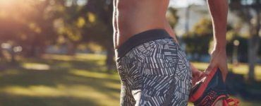 Frau draußen im Park mit Sixpack von der Seite hält einen Fuß und dehnt sich