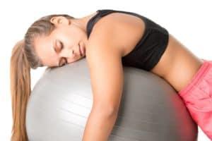 Junge Frau in Sportkleidung schläft beim Training auf einem Pezziball