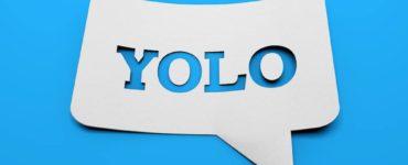 weißes schild mit YOLO in sprechblasenform vor blauem Hintergrund