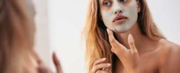 Junge Frau vor dem Badezimmerspiegel trägt eine Hautpflegemaske im Gesicht auf