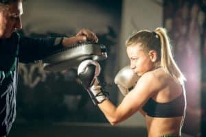 Junge Frau hochkonzentriert macht Boxtraining