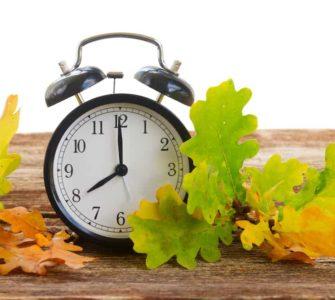 Wecker auf Holztisch mit buntem Herbstlaub