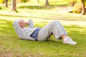 Ältere fitte Frau in Sportkleidung im Park liegt auf Wiese und macht Crunches