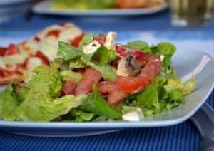 Grüner Sommersalat mit Tomaten, Feta und Pilzen an einem Mango-Pfirsich-Dressing