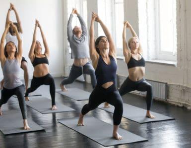 Eine Yoga Gruppe macht Krieger-Übungen im Stand.
